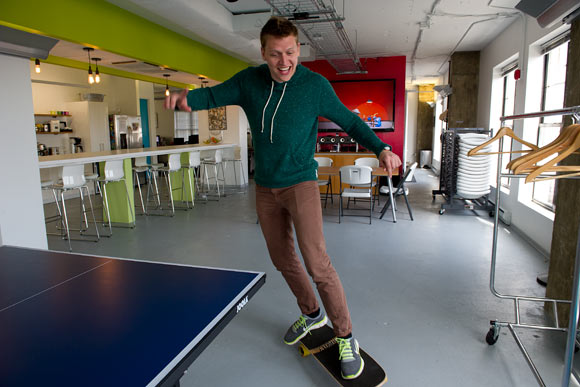 Creative director Zach Goodwin skateboards through the office
