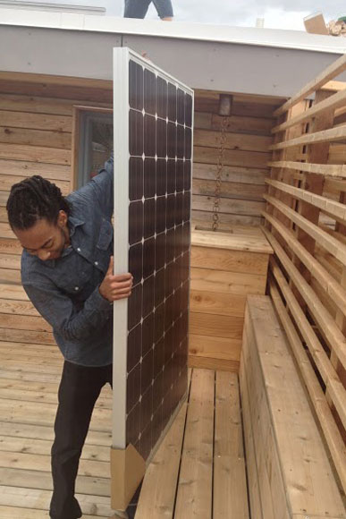 A worker installs solar panels on a home