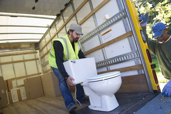 A Community Forklift staffer loads a toilet from a NW home onto the Forklift's truck