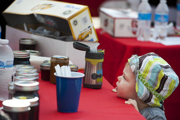 Eighteen-month-old Caden Kiraly peeks up at the table where his mother, Stacia, is judging jam at the DC State Fair