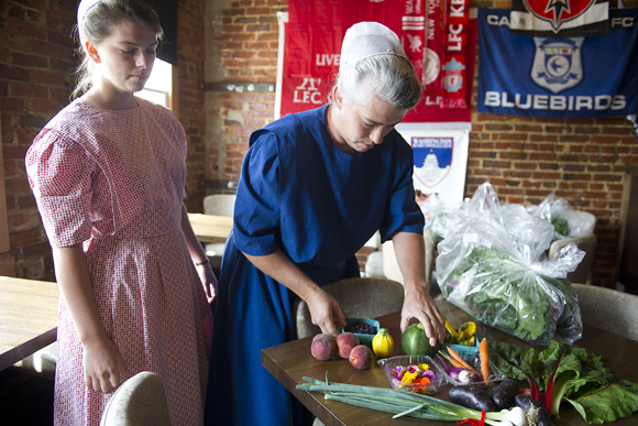 "Doreen and Kimberly Shank, who run Hickory Ridge Farm with their family in Franklin County, Penn., unload fresh fruits and veggies at The Queen Vic on H St. NE. The Queen Vic is piloting a ""Table to Farm"" program"