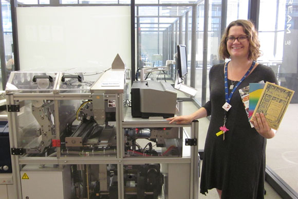 Digital commons librarian Emily Graves poses in front the Espresso Book Machine with copies of self published books created at the library